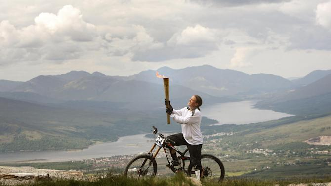 This image made available by LOCOG shows Mountain Biker Tracy Moseley carries the Olympic Flame on the Nevis Range, a mountain ski resort in the The Highlands of Scotland near Ben Nevis and Fort William on Day 22 of the Torch Relay leg Saturday June 9, 2012.   (AP Photo/Danny Lawson/PA Wire)
