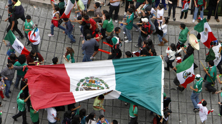 Fans of Mexico's soccer team carry their nation's flag at the Angel of Independence monument to celebrate their team's 2-1 victory over Brazil and winning of the gold medal for men's soccer at the London 2012 Summer Olympics, in Mexico City, Saturday, Aug. 11, 2012. (AP Photo/Marco Ugarte)