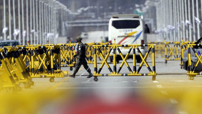 A South Korean Army soldier controls traffic at the barricaded Unification Bridge near the border village of Panmunjom, that has separated the two Koreas since the Korean War, in Paju, north of Seoul, South Korea, Sunday, April 7, 2013. South Korea said its top military officer has put off a plan to visit Washington due to current tension with North Korea. (AP Photo/Lee Jin-man)