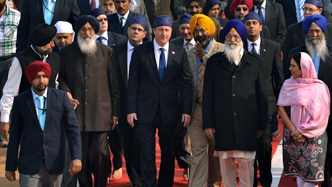 British Prime Minister David Cameron, center, visits the Golden Temple, Sikh's holiest shrine, along with Chief Minister of Punjab state Parkash Singh Badal, second from left wearing glasses, in Amritsar, India, Wednesday, Feb. 20, 2013. Cameron also laid a mourning wreath at Jallianwala Bagh, the site of a notorious 1919 massacre of hundreds of Indians by British colonial forces. More than 300 Indians were killed during the massacre on unarmed Indians attending a rally, which galvanized the national independence movement. (AP Photo/Sanjeev Syal)