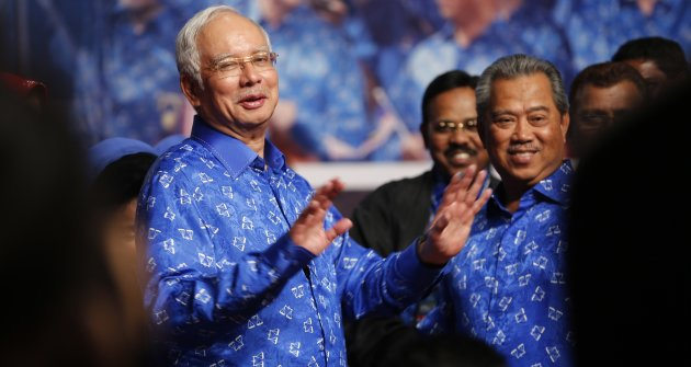 Malaysia's Prime Minister Najib Razak (L) and his deputy Muhyiddin Yassin share a light moment after winning the elections at his party headquarters in Kuala Lumpur early May 6, 2013. Malaysia's governing coalition won a tight national election on Sunday to extend its 56-year rule, fending off an opposition alliance that pledged to clean up politics and end race-based policies in Southeast Asia's third-largest economy. REUTERS/Bazuki Muhammad (MALAYSIA - Tags: POLITICS ELECTIONS)