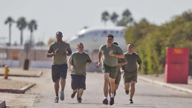 """In a Thursday, Oct. 17, 2013 photo, a group of sailors and Marines who failed the so-called """"tape test'' are led by an instructor on a three mile run as they work to improve their fitness and remain in the military, at the Marine Corps Recruit Depot in San Diego. Doctors say a number of military personnel are turning to liposuction to remove excess fat from around the waist so they can pass the Pentagon's body fat test. Some service members say they have no other choice because the Defense Department's method of estimating body fat is weeding out not just flabby physiques but bulkier, muscular builds. A number of fitness experts and doctors agree, and they're calling for the military's fitness standards to be revamped. (AP Photo/Lenny Ignelzi)"""
