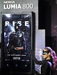 "A model in costume poses besides a large model of the Nokia Lumia 800 Dark Knight Rises (DKR) limited edition Windows phone during its launch in Bangalore on July 6. US talk show host David Letterman triggered online wrath from movie fans Friday, after apparently giving away a key plot twist in the new ""Dark Knight"" movie"