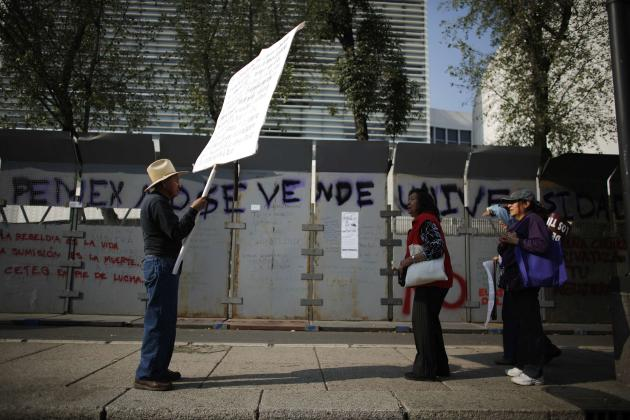 A demonstrator holds up a sign for passers-by to read as he protests against an energy reform bill outside the Senate building in Mexico City