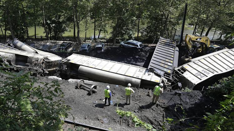 Officials inspect part of a CSX freight train that derailed alongside a parking lot overnight in Ellicott City, Md., Tuesday, Aug. 21, 2012. Authorities say the train, hauling coal from West Virginia to Maryland, derailed and fell from a bridge near Baltimore, killing two college students who were on the tracks. Howard County officials say 21 of the train's 80 cars flipped over around midnight Monday.  (AP Photo/Patrick Semansky)