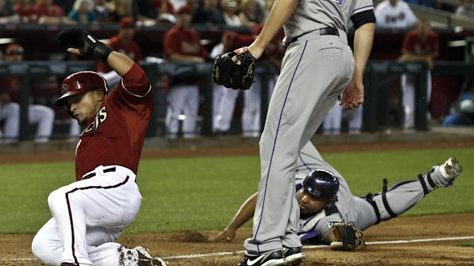Gerardo Parra de los Diamondbacks de Arizona, izquierda, anota una carrera en el tercer inning ante los Rockies de Colorado el domingo 28 de abril de 2013. (AP Foto/Ross D. Franklin)