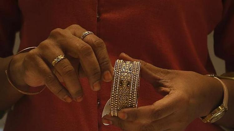 An employee shows a gold bangle to a customer inside a jewellery showroom in Mumbai August 30, 2013. REUTERS/Danish Siddiqui