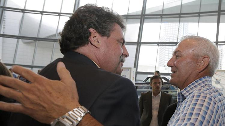 Dale Jarrett, right, is congratulated by NASCAR president Mike Helton, left, after being named to the next class of inductees during an announcement at the NASCAR Hall of Fame in Charlotte, N.C., Wednesday, May 22, 2013. (AP Photo/Chuck Burton)