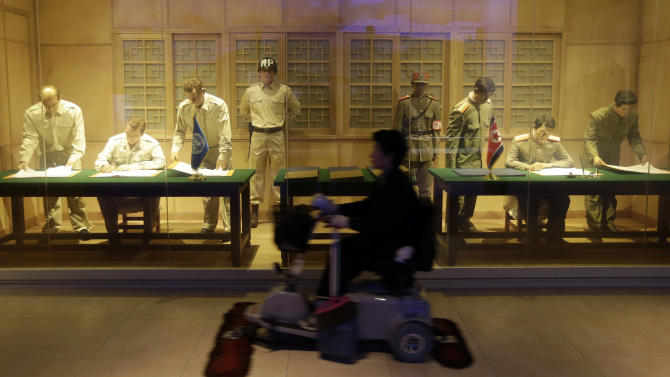A cleaner rides a cart in front of an exhibit depicting the 1953 cease-fire agreement of the Korean War at the Korea War Memorial Museum in Seoul, South Korea, Wednesday, March 6, 2013. North Korea's military is vowing to cancel the 1953 cease-fire that ended the Korean War, straining already frayed ties between Washington and Pyongyang as the United Nations moves to impose punishing sanctions over the North's recent nuclear test. (AP Photo/Lee Jin-man)