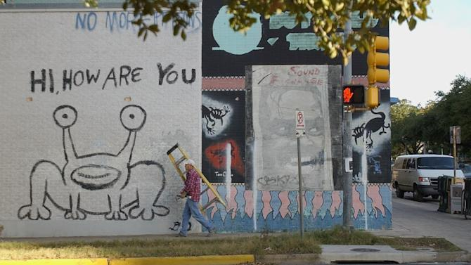 """FILE - In this Friday, Jan. 9, 2004, file photo, carpenter Lee Blair carries a ladder near a well-known mural of a frog-like creature saying """"Hi, How Are You,"""" in Austin, Texas. According to an arrest affidavit, 32-year-old Rebecca Guest was arrested Christmas Eve and charged with a Class A misdemeanor after police saw her defacing the mural, which was painted by Texas singer-songwriter Daniel Johnston. An obscene word was spray-painted several times on the mural. (AP Photo/Harry Cabluck, File)"""