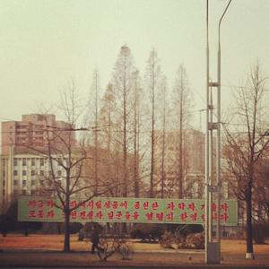 In this photo posted on Instagram, a man walks in Pyongyang, North Korea, under a new roadside banner referring to North Korea's controversial Feb. 12 nuclear test Monday, Feb. 25, 2013. Tweeting and uploading to Instagram is pretty ordinary stuff in the world of social media, but revolutionary for North Korea. (AP Photo/Jean H. Lee)