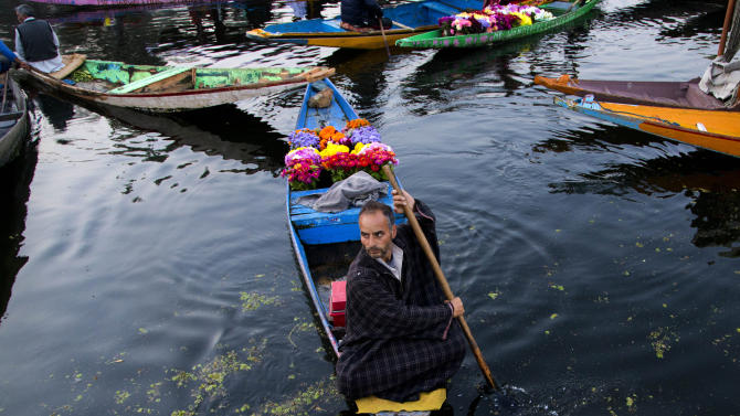 In this Oct. 6, 2015 photo, a Kashmiri flower vendor rows his boat at the floating vegetable market on Dal lake in Srinagar, Indian controlled Kashmir. Vegetables traded in this floating market are supplied to Srinagar and many towns across the Kashmir valley. It's one of the major sources of income for the lake dwellers who spend years carefully nurturing their floating gardens from the weed and rich soil extracted from the lake bed. Sometimes a boat will weave through, selling flowers to the tourists who stay in the houseboats. (AP Photo/Dar Yasin, File)
