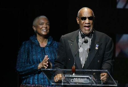 Comedian Bill Cosby addresses the crowd in front of his wife, Camille Cosby, after being honored during the Apollo Theatre's 75th anniversary gala in New York