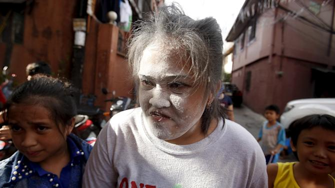 A girl is pictured with flour on her face after winning a coin grabbing contest during a celebration of religious patron Nuestro Senor Jesucristo in Quezon city