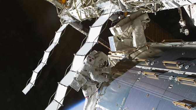 In this image provided by NASA astronaut Nicole Stott, Expedition 20 flight engineer, participates in the STS-128 mission's first session of extravehicular activity on the International Space Station Sept. 1, 2009. Two deployed radiators are visible behind Stott. The International Space Station has a radiator leak in its power system. The outpost's commander calls the situation serious, but not life-threatening. The six-member crew on Thursday May 9, 2013 noticed white flakes of ammonia leaking out of the station.  (AP Photo/NASA)