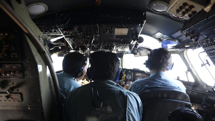 Vietnamese Air Force officers sit in the cockpit of a search and rescue aircraft as they fly over the search area for a missing Malaysia Airlines plane