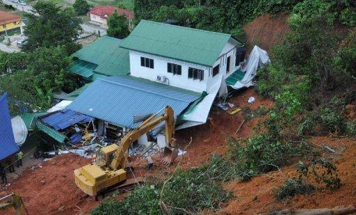 Emergency teams work to clear the damage created by a landslide that destroyed an orphanage in the Malaysian province of Hulu Langat. A close-knit village on the outskirts of the Malaysian capital was grieving for the deaths of 16 people, mostly children, after an orphanage was hit by a devastating landslide