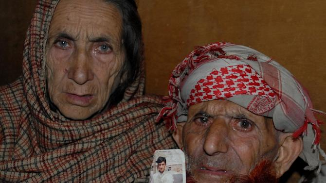 The parents of convicted killer Shafqat Hussain hold a photograph of their son, during a press conference in Muzaffarabad, on March 12, 2015
