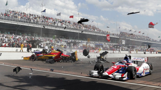 Sebastian Saavedra, left, of Colombia, is hit by Mikhail Aleshin, of Russia, on the start of the inaugural Grand Prix of Indianapolis IndyCar auto race at the Indianapolis Motor Speedway in Indianapolis, Saturday, May 10, 2014. Takuma Sato, right, of Japan, drives past accident. (AP Photo/Robert Baker)