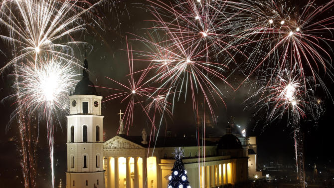Fireworks light the sky above the Cathedral Square in Vilnius shortly after midnight, greeting the New Year, Tuesday, Jan. 1, 2013. (AP Photo/Mindaugas Kulbis)