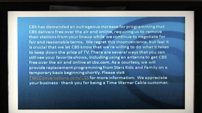 FILE - In this Friday, Aug. 2,2013, file photo, a television screen shows the CBS channel with an announcement by Time Warner Cable in Los Angeles. Three million Time Warner Cable customers in New York, Los Angeles and Dallas are without the CBS channel, as the cable provider says it is dropping the network in a dispute over fees. (AP Photo/Nick Ut, File)