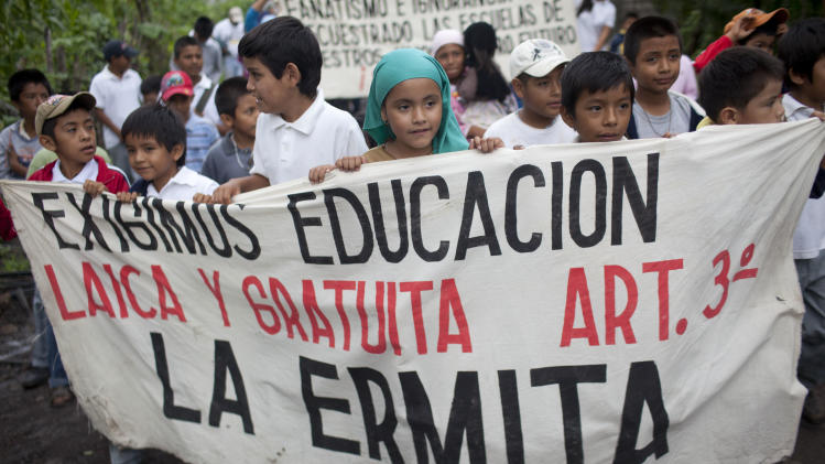 Students carry a banner during a protest in favor of secular education in Nueva Jerusalen, Mexico, Monday, Aug. 27, 2012. Mexican authorities are still unable to overcome the resistance of a sect in this town which has refused to allow public school teachers to hold classes. (AP Photo/Alexandre Meneghini)
