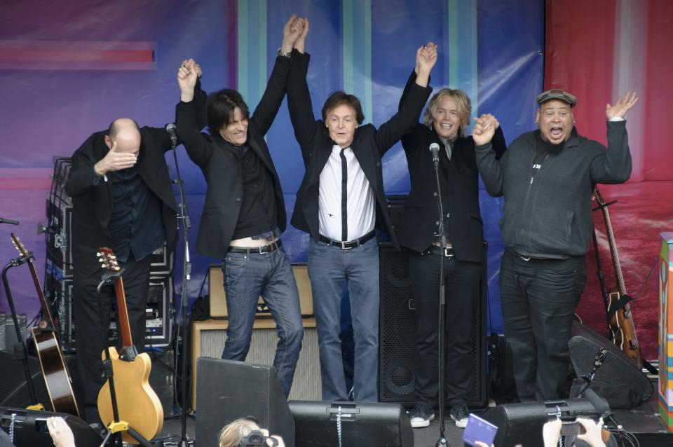 British singer Sir Paul McCartney, centre, and his band acknowledge the crowd after performing in Covent Garden, London, Friday, Oct. 18, 2013. The surprise gig lasted for 20 minutes during lunchtime following a similar appearance in New York last Friday. (Photo by Jonathan Short/Invision/AP)