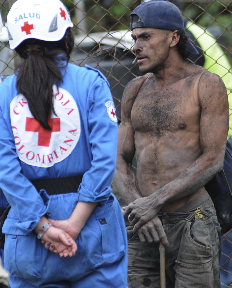 "A miner speaks to a paramedic outside ""El Desespero"" coal mine in Angelopolis, northern Colombia, Thursday, March 8, 2012.  At least four miners died and five others are still missing after workers hit a source of water that flooded and collapsed the small mine on Wednesday.  (AP Photo/Luis Benavides)"