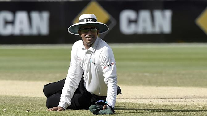 Umpire Kumar Dharmasena of Sri Lanka smiles after he dove to the ground to avoid a struck ball on the third day of the cricket test match between India and Australia in Melbourne, Australia, Sunday, Dec. 28, 2014. At Stumps India are 4 for 462 in reply to Australia's first innings of 530 all out. (AP Photo/Andy Brownbill)