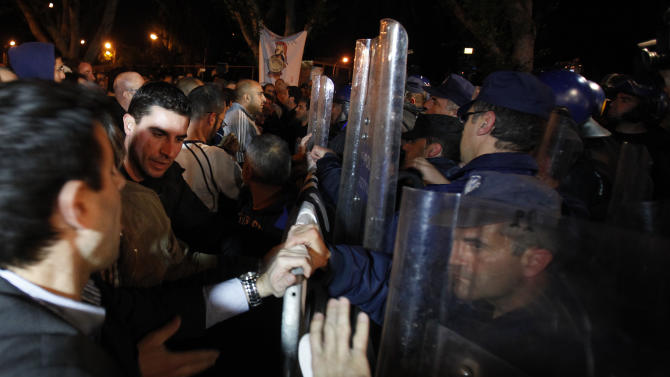 Employees of Laiki bank, left, push barriers as riot police try to stop them during an anti-bailout protest outside of Cypriot parliament in capital Nicosia, Cyprus, Thursday, March 21, 2013. Cypriot officials were scrambling Thursday to cement a revised plan to raise funds demanded by international creditors in exchange for an international bailout Thursday, with time running out fast and the country's economy just days away from potential ruin. (AP Photo/Petros Karadjias)