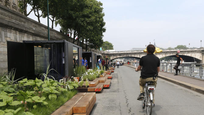A man rides his bicycle along the renovated Left Bank of the River Seine in Paris where a new promenade has been inaugurated, Wednesday, June 19, 2013 . The 2.3 km (1.4 miles) walkway offers gardens, cafes, culture and sports activities. (AP Photo/Jacques Brinon)