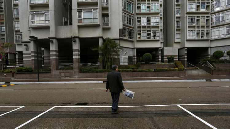 A man walks past a parking spot outside a residential building in Hong Kong Tuesday, Nov. 27, 2012. Investors looking for new areas to park their cash in Hong Kong are driving up prices for parking spaces, sparking fears of a bubble in the Asian financial center. Prices for parking spots in Hong Kong are nearing historic highs, the side effect of government curbs to cool the housing market amid worries of overheating following the latest round of economic stimulus in the U.S. (AP Photo/Vincent Yu)