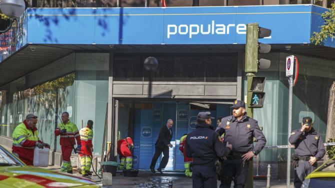 Policemen stand guard as workers clean the entrance of the headquarters of Spain's ruling People's Party in Madrid