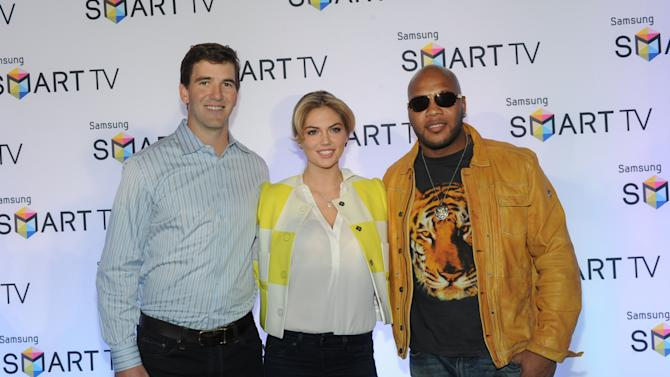Model Kate Upton, center, football quarterback Eli Manning, left, and Flo Rida help Samsung showcase its 2013 line of Smart TVs, Wednesday, March 20, 2013, in New York. Samsung's new line allows the viewer to discover more of the TV they love with a simpler, more personalized and smarter way of watching TV.  (Photo by Diane Bondareff/Invision for Samsung/AP Images)