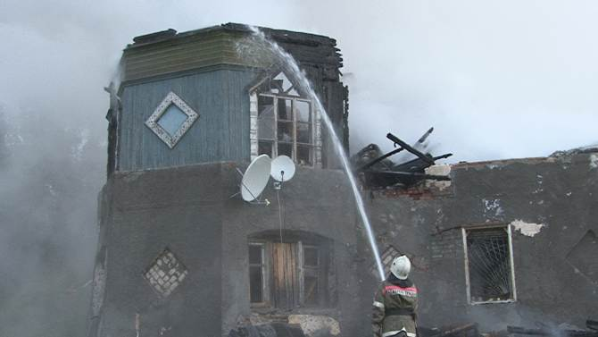 A firefighter works near a psychiatric hospital destroyed by fire in the Novgorod region town of Luka