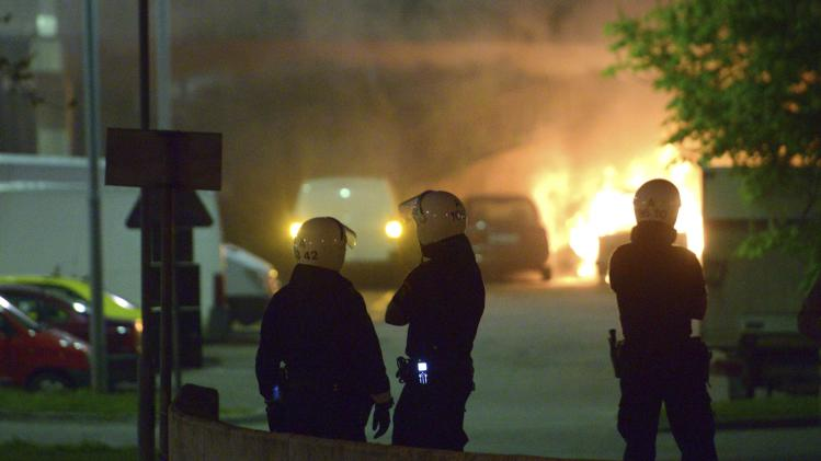 Police officers stand guard in a street during a riot in Stockholm, Sweden, Monday, May 20, 2013. Gangs of youth apparently angered by the police shooting death of an elderly man hurled rocks at police and set cars and buildings on fire in a Stockholm suburb, forcing the evacuation of an apartment block. (AP Photo Johan Nilsson) SWEDEN OUT
