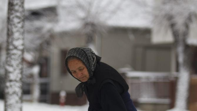 An elderly woman, Ferencne Szmodics shovels snow on the sidewalk in front of her house in Nagykanizsa, 208 kms southwest of Budapest, Hungary, Sunday, Dec. 28, 2014, after snow fell for the first time in the current winter season in Hungary. (AP Photo/MTI, Gyorgy Varga)