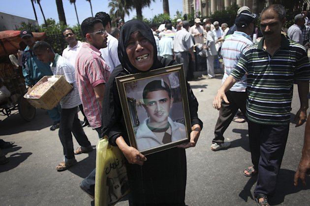 An Egyptian protesters holds a picture of a relative killed in the 2011 Egyptian revolution during a demonstration against the Supreme Constitutional Court rulings in Alexandria, Egypt, June 15, 2012. Judges appointed by Hosni Mubarak dissolved the Islamist-dominated parliament Thursday and ruled his former prime minister eligible for the presidential runoff election this weekend, setting the stage for the military and remnants of the old regime to stay in power. (AP Photo/Manu Brabo)