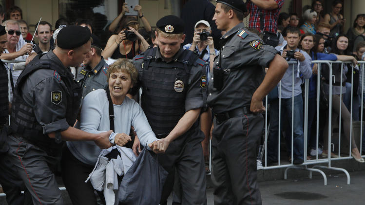 Police officers detain a supporter of the Russian punk group Pussy Riot outside a court in Moscow, Russia, Friday, Aug. 17, 2012. A Moscow judge has sentenced each of three members of the provocative punk band Pussy Riot to two years in prison on hooliganism charges following a trial that has drawn international outrage as an emblem of Russia's intolerance to dissent. (AP Photo/Alexander Zemlianichenko)