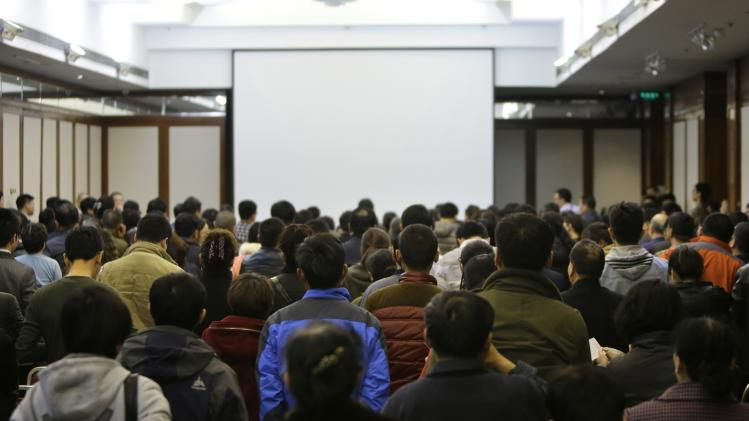 Relatives of passengers aboard Malaysia Airline MH370 stand up to show distrust in the Airline a during a meeting at Lido Hotel in Beijing