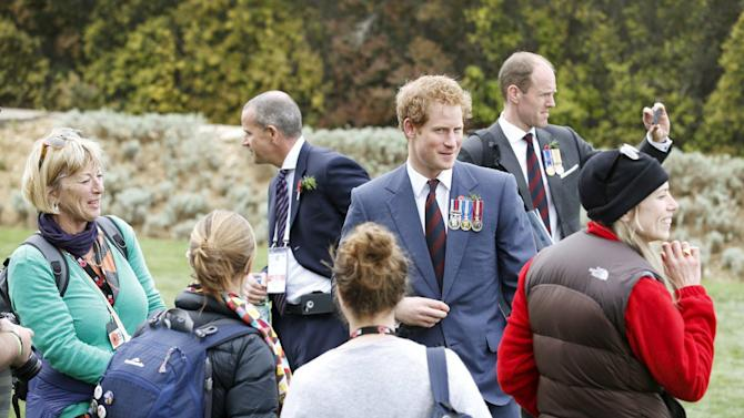 Britain's Prince Harry chats with Australian visitors during a visit to The Nek Cemetery with Prince Charles, Prince of Wales, in Gallipoli