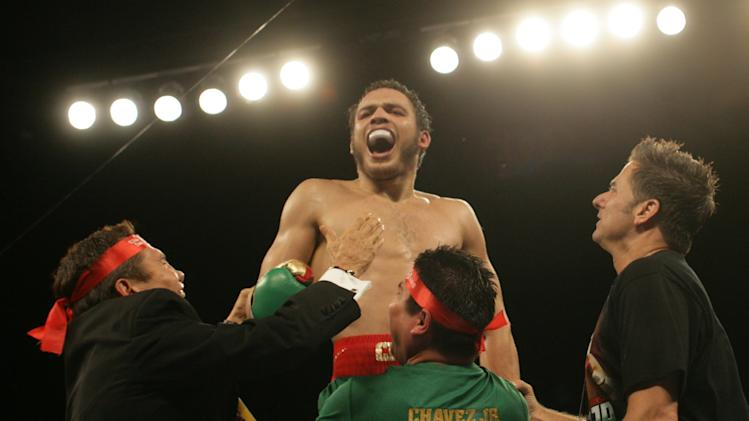 Julio Cesar Chavez, Jr., top, screamed in celebration as his father, Julio Cesar Chavez, left, joined in the celebration of Junior's victory over Andy Lee in  their WBC middleweight title bout Saturday June 16, 2012 in El Paso, Texas. (AP Photo/El Paso Times, Victor Calzada)