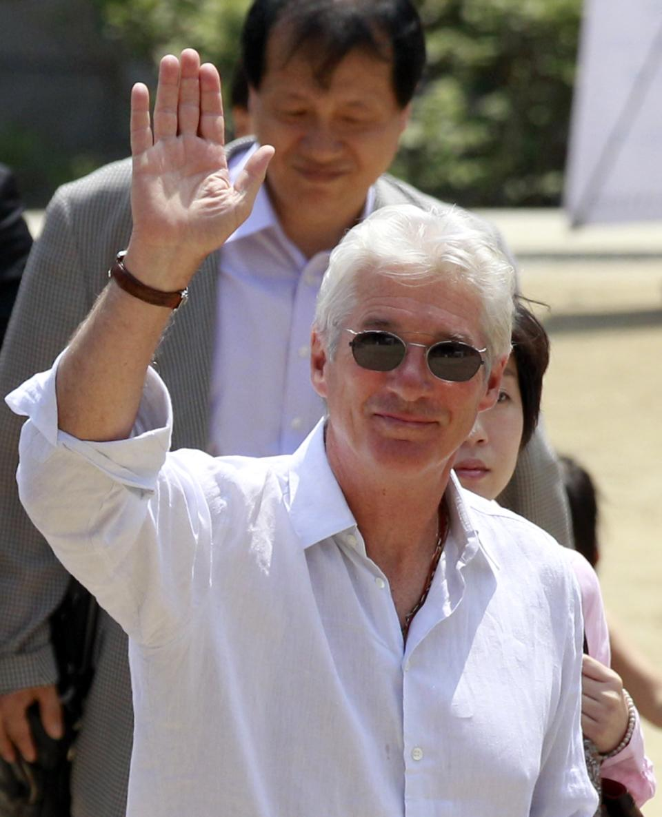 U.S. actor Richard Gere waves to Buddhists at the Chogye temple in Seoul, South Korea, Tuesday, June 21, 2011. Gere is on a six-day visit in the county to promote his photo exhibition and tour Buddhist temples. (AP Photo/ Lee Jin-man)