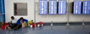 Two women travelers sit on the floor at the Miami International…