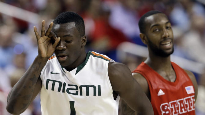 Miami's Durand Scott (1) reacts after making a basket as he runs past North Carolina State's C.J. Leslie (5) during the first half of an NCAA college basketball game in the semifinals of the Atlantic Coast Conference tournament in Greensboro, N.C., Saturday, March 16, 2013. (AP Photo/Gerry Broome)
