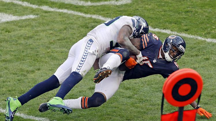 Chicago Bears wide receiver Brandon Marshall (15) is tackled by a Seattle Seahawks defender in the second half of an NFL football game in Chicago, Sunday, Dec. 2, 2012. (AP Photo/Charles Rex Arbogast)
