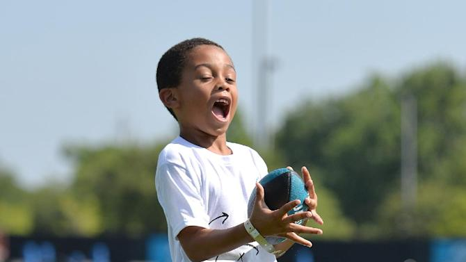 Eorbin Ellis, 6, catches a pass while working with the wide receivers at an NFL football Jacksonville Jaguars' Got Skills Rookie Day on Friday, June 20, 2014, in Jacksonville, Fla