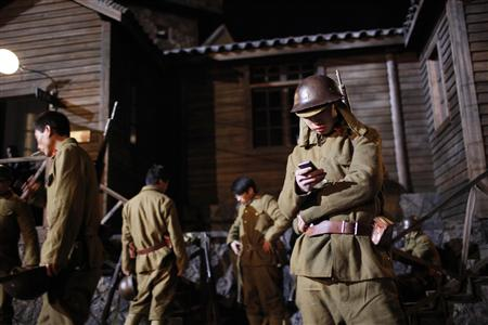 An actor in a Japanese military uniform checks his mobile phone during filming in Hengdian Film City