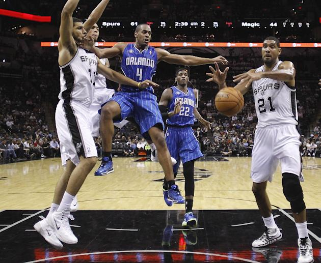 Orlando Magic's Arron Afflalo (4) is stripped of the ball by San Antonio Spurs' Jeff Ayres (11) as Tim Duncan (21) grabs the loose ball during the first half of a preseason NBA basketball game, Tuesda