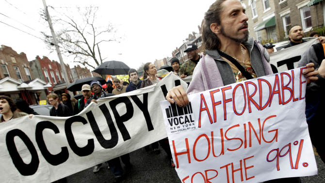 FILE - In this Dec. 6, 2011 file photo, Occupy Wall Street activists march during a tour of foreclosed homes in the East New York neighborhood of the Brooklyn borough of New York. New York Mayor Bill de Blasio has an ambitious plan to build or preserve 200,000 affordable units of housing over the next 10 years for lower-income New Yorkers, a staggering number that would house a population bigger than cities such as Atlanta or Minneapolis. (AP Photo/Mary Altaffer, File)